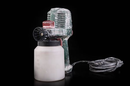 Dirty electric paint sprayer. DIY painting accessories. Dark background. Imagens