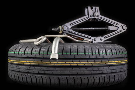 Spare wheel with a set of keys. Spare wheel replacement accessories for passenger cars. Dark background.