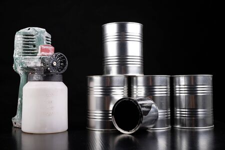 Dirty electric paint sprayer and paint cans. DIY painting accessories. Dark background.