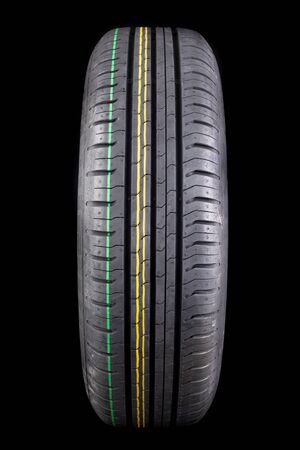 New black tire with deep tread. Car tires. Dark background.