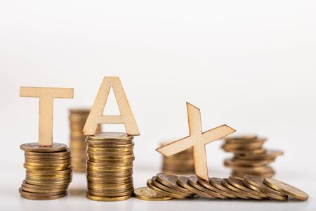 TAX inscription made of wooden letters on coin posts. Symbol of tax collection from the public. Light background.