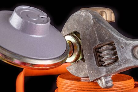 Gas cylinder and propane-butane gas reducer. Installation of a special hose for a metal cylinder. Dark background.