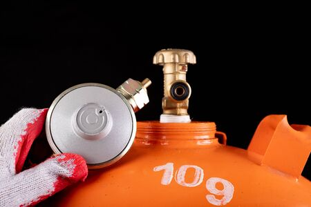 Gas cylinder and propane-butane gas reducer. Accessories for home gas supply. Dark background.