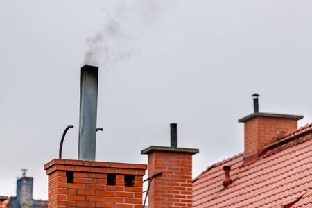 Chimneys on the roofs of single-family houses. Smoke rising over the roofs of a small town. Autumn time.