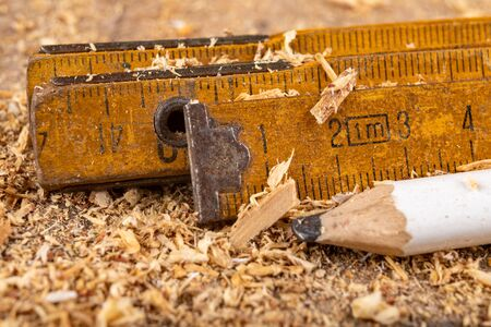 Carpentry measure in sawdust on a wooden table. Small carpentry work in a home workshop. Dark background.