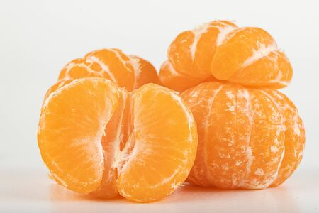 Tasty ripe mandarin on a white table. Peeled citruses. Light background.