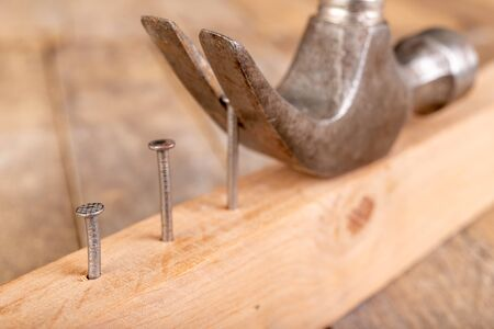 Pulling out nails from a piece of wood using a carpenter's hammer. Small carpentry work in the workshop . Dark background.
