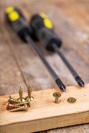 Wood screws and a screwdriver on a piece of wood. Carpentry work in a home workshop. Dark background.