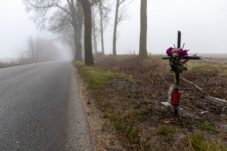 Asphalt road in the fog. Public road and cross commemorating a fatal accident. Autumn season.