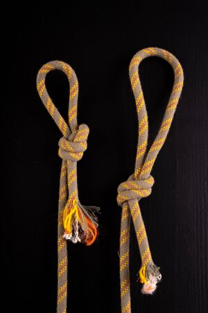 Two loops made of thick rope. Loop-shaped knot. Dark background.