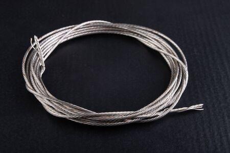 Steel rope coiled in a loop. Accessories in a home workshop. Dark background