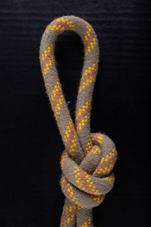 Loop made of thick rope. Loop-shaped knot. Dark background