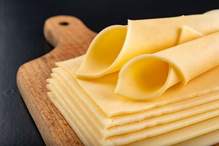 Slices of yellow cheese on a wooden board. Food from the market on the kitchen table. Dark background.