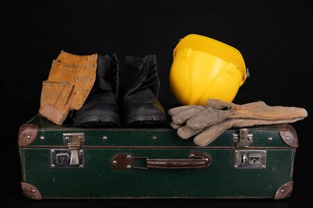 Protective clothing and an old suitcase. Economic emigration of production workers. Dark background.