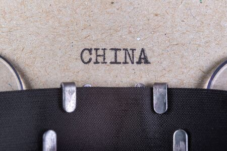 The word china written in typewriter font. The inscription in the old style on gray paper. Grey background.