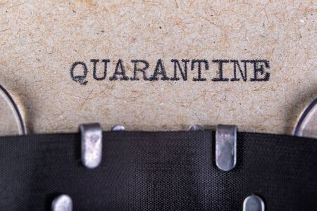 The word quarantine written in typewriter font. The inscription in the old style on gray paper. Grey background.