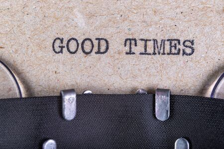 The words good times written in typewriter font. The inscription in the old style on gray paper. Grey background.