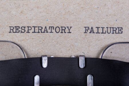 The word respiratory failure written in typewriter font. The inscription in the old style on gray paper. Grey background.
