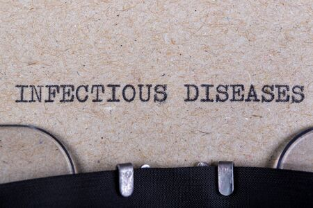 The word infectious diseases written in typewriter font. The inscription in the old style on gray paper. Grey background.