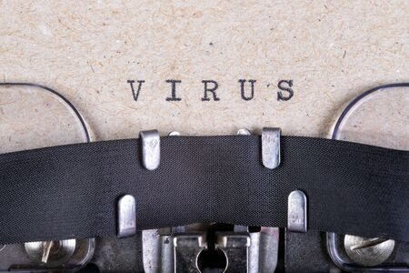 The word virus written in typewriter font. The inscription in the old style on gray paper. Grey background.
