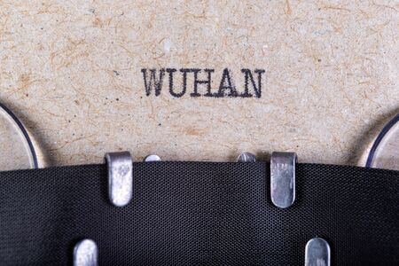 The word wuhan written in typewriter font. The inscription in the old style on gray paper. Grey background. Stock Photo