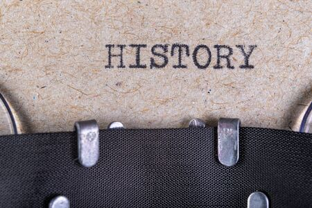The word history written in typewriter font. The inscription in the old style on gray paper. Grey background.