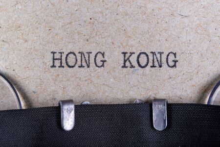 The word hong kong written in typewriter font. The inscription in the old style on gray paper. Grey background. Stock Photo