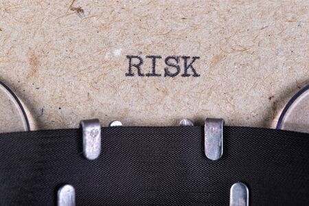 The word risk written in typewriter font. The inscription in the old style on gray paper. Grey background.