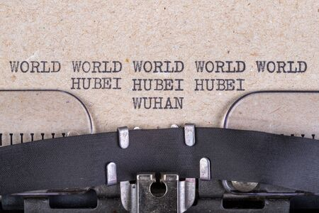 The words world, hubei, wuhan written in typewriter font. The inscription in the old style on gray paper. Grey background. Stock Photo