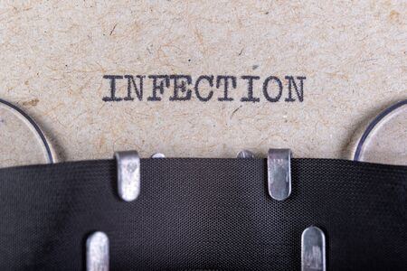 The word infectious written in typewriter font. The inscription in the old style on gray paper. Grey background.