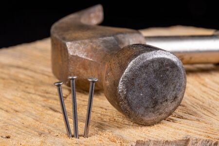 Three nails stuck in a piece of wood. Carpentry work in the workshop. Dark background. 스톡 콘텐츠