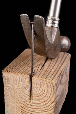 Pulling out a nail with a carpenter's hammer. Carpentry accessories on a workshop table. Dark background.