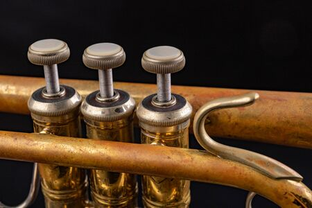 Details of an old patina covered trumpet. Musical instrument shown in magnification. Dark background.