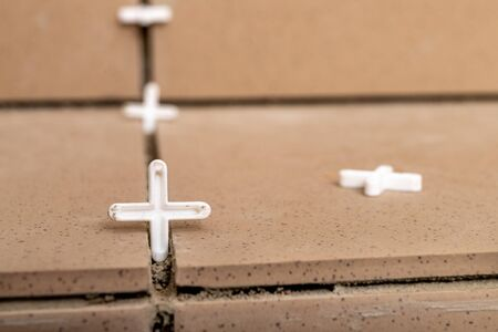 Plastic crosses that position the tiles when laying. The process of sticking porcelain tiles. Light background.