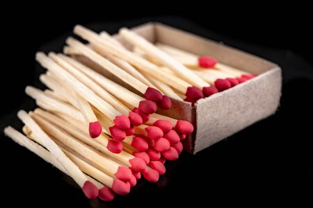 Matches in gray paper boxes. Wooden sticks with sulfur on the tip to ignite the flame. Dark background.