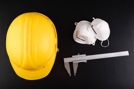 Helmet, caliper and protective mask on a dark table. Protection against adverse conditions at work. Dark background. Archivio Fotografico