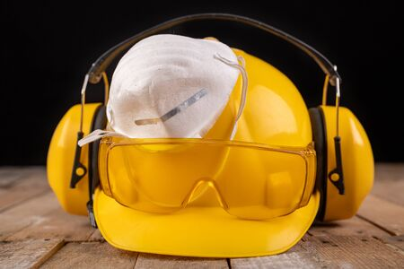 Workwear and protective mask on a wooden table. Protective accessories for the production worker. Dark background.