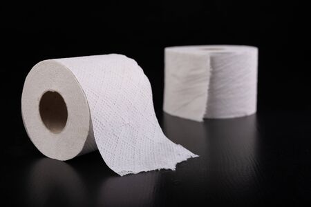 White toilet paper on a dark table. Articles for daily hygiene. Black background.