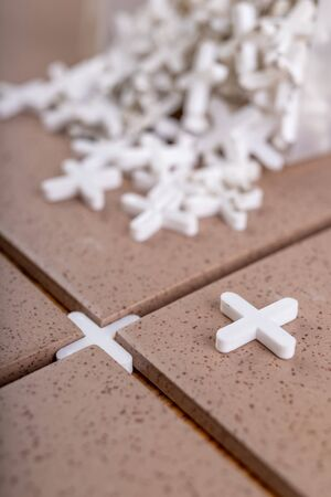 Industrial tiles and plastic crosses for tiling. Accessories for construction workers. Workplace - workshop. Archivio Fotografico