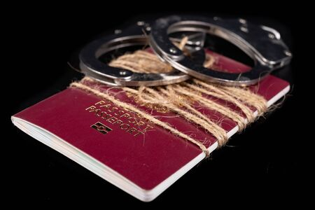 A passport tied with string and handcuffs. No travel during pandemics. Dark background. Imagens