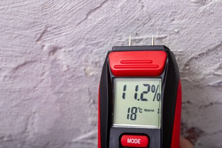 Plaster moisture measurement using an electronic meter. Measurements in the home workshop. Light background.