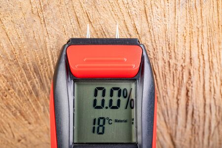 Wood moisture measurement using an electronic meter. Measurements in the home workshop. Light background.