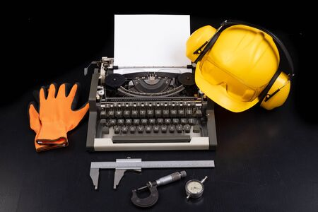 A construction helmet on an old typewriter. Measuring instruments used in heavy industry. Dark background. Archivio Fotografico