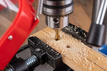 Drilling in wood with professional tools. Work on a bench drill. Workplace workshop. Standard-Bild
