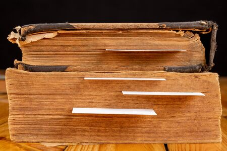 Bookmark in an old book on a wooden table. Marked places of important places and quotes. Light background.