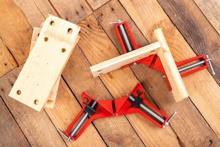 Joining wood using a carpentry clamp. Small carpentry work. Workplace - workshop. 免版税图像