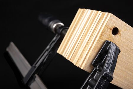 Wooden plywood panels in a carpenter's clamp. Wood panels prepared for gluing with carpentry glue. Workplace workshop.