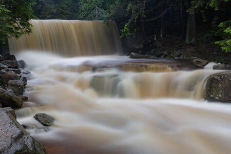 Waterfall in a mountain area. Mountain river flowing through rocky terrain. Summer season.