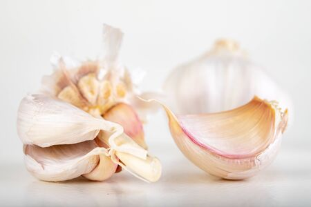 A whole head of garlic and a few cloves of garlic. Vegetables used in home cooking. Light background.