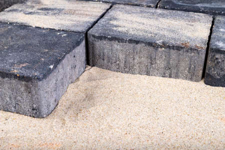 Laying paving stones on sand. Minor paving work in a home environment. Garden workplace. Stock Photo